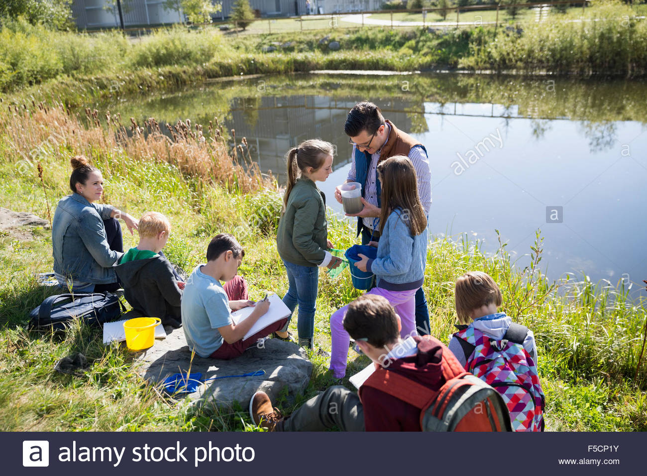 Science teacher and students at pond field trip - Stock Image