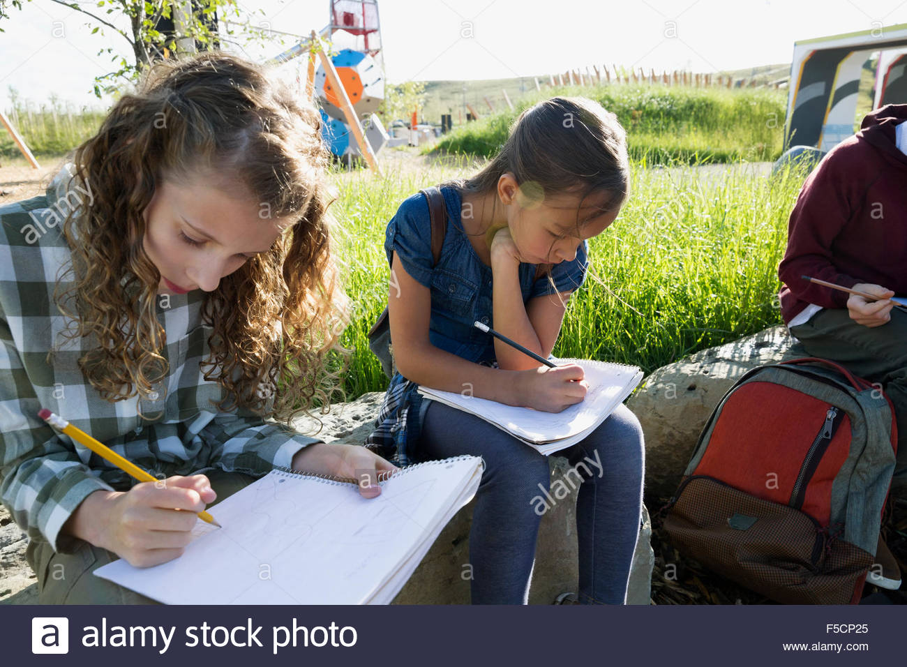 Students doing homework at sunny playground - Stock Image