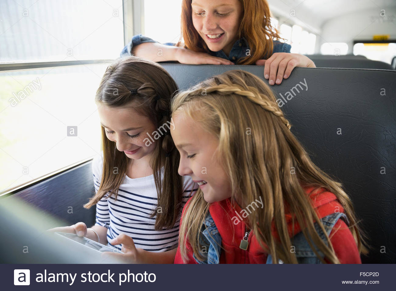 Schoolgirls texting with cell phone on school bus - Stock Image
