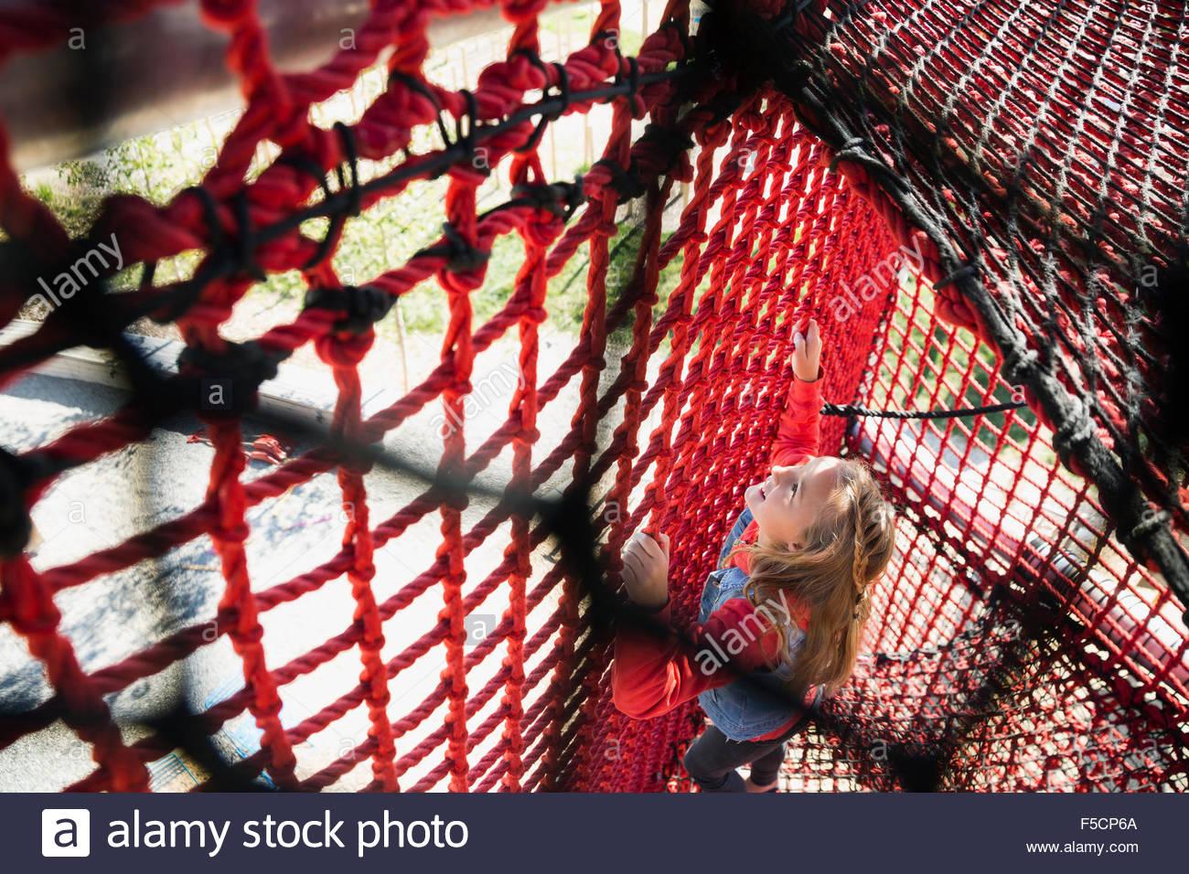 Girl climbing rope net at playground Stock Photo