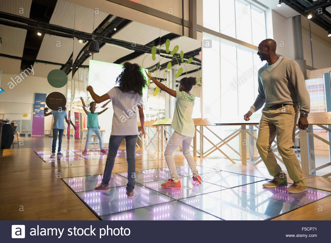 Father watching daughters dance in science center - Stock Image