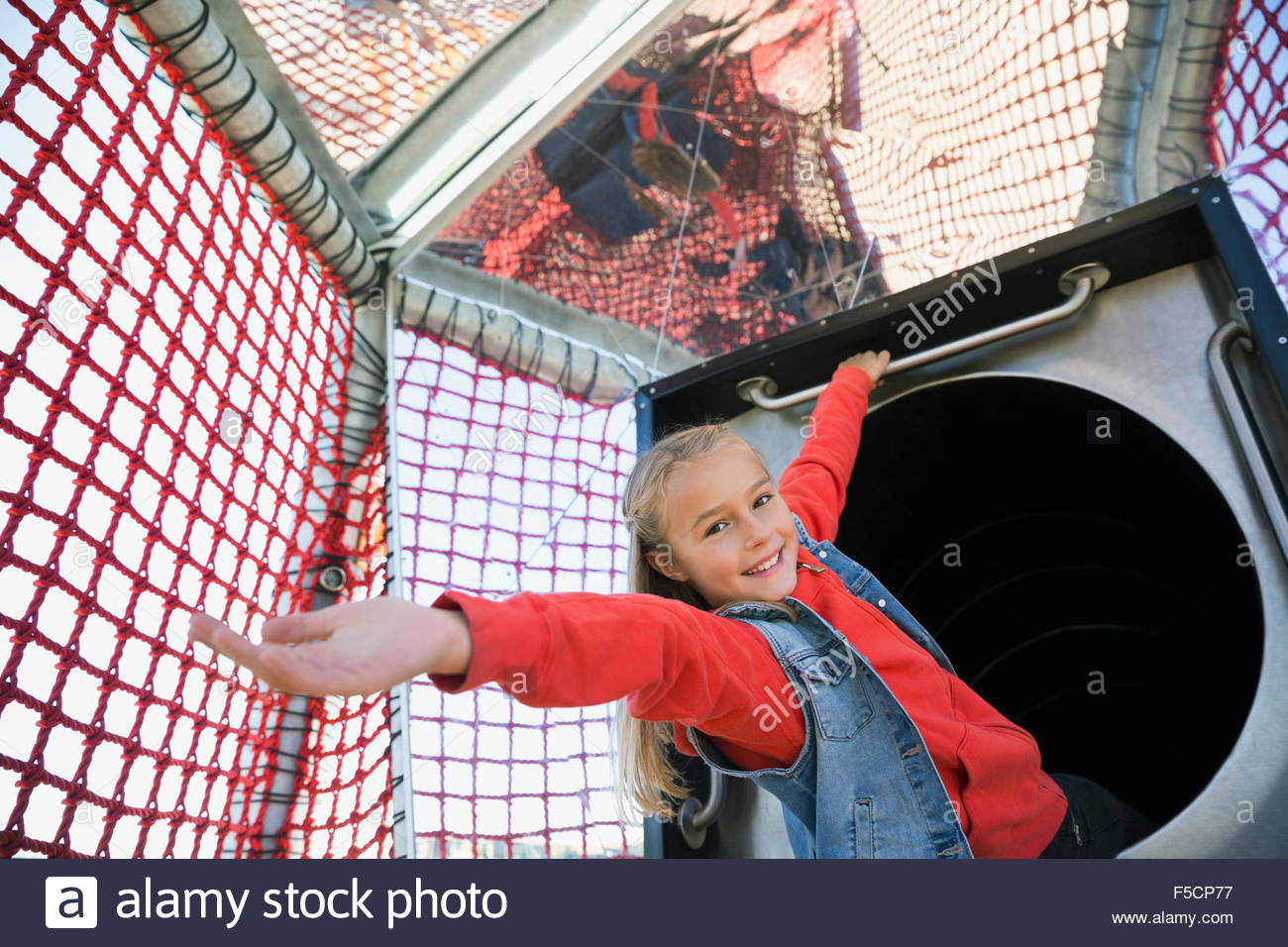 Portrait smiling girl with arms outstretched at playground - Stock Image