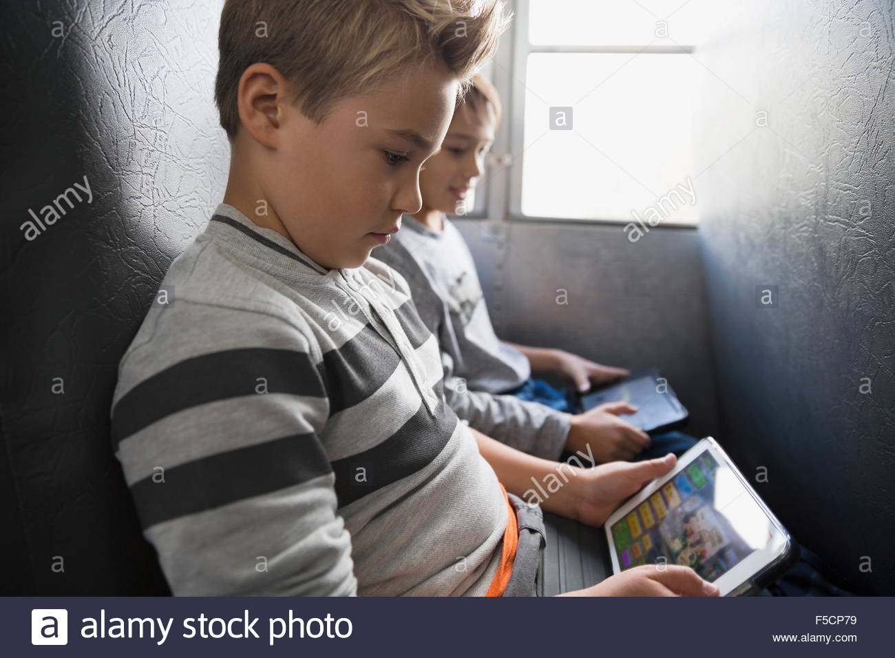 Schoolboy playing game on digital tablet school bus Stock Photo