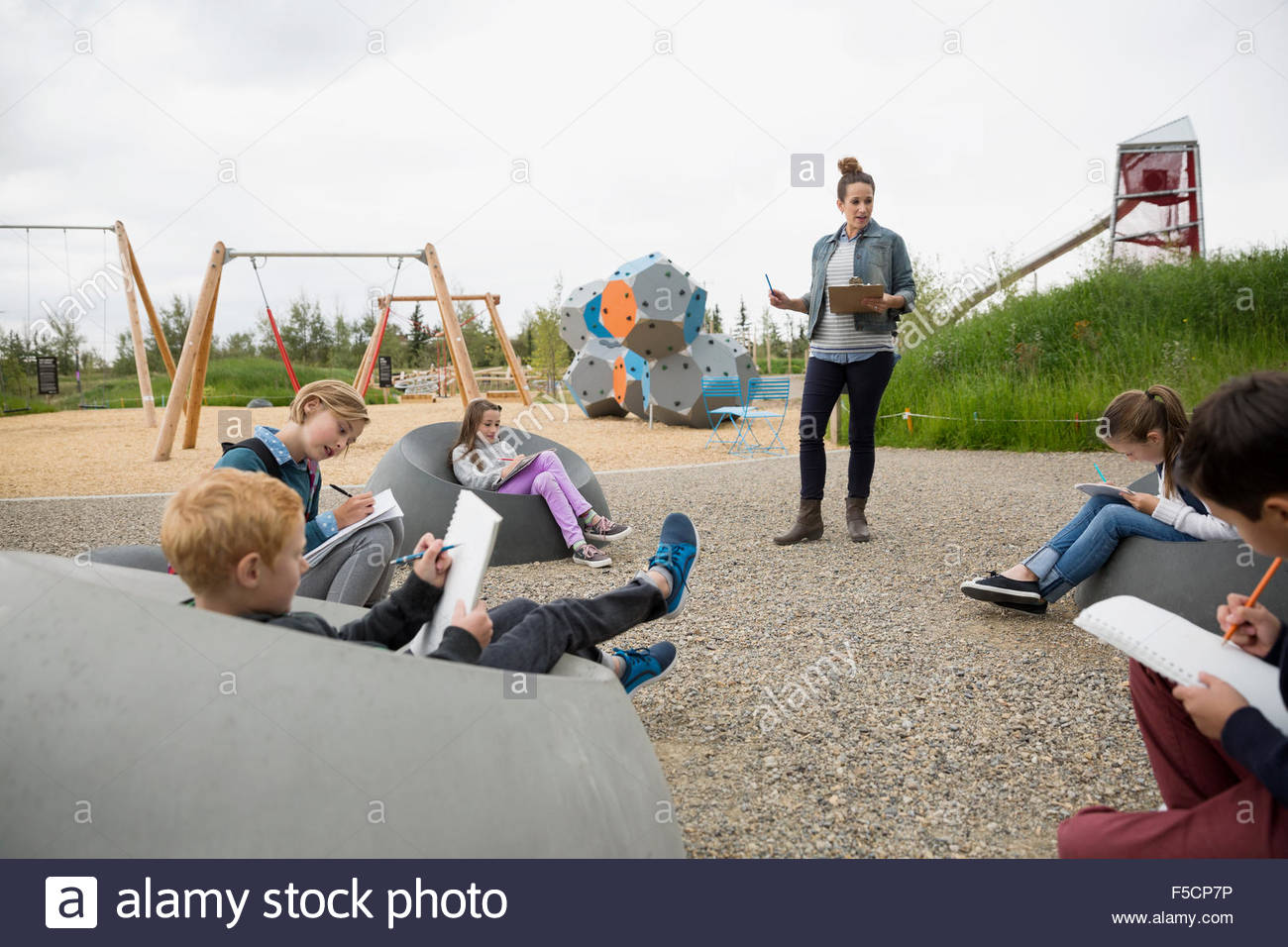 Teacher guiding students with notebooks at playground - Stock Image