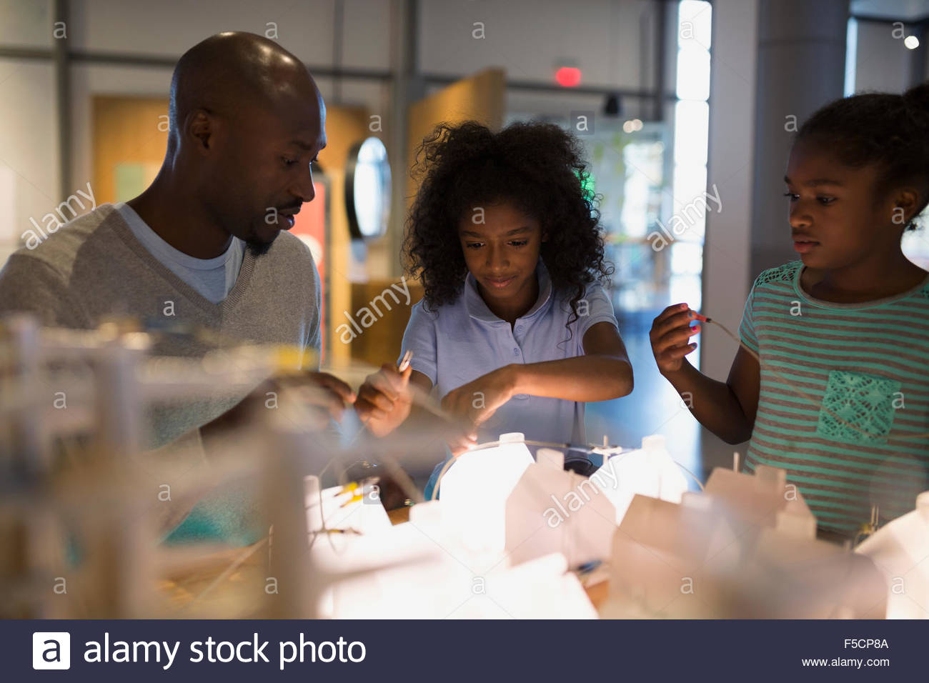 Father and daughters playing electricity grid science center - Stock Image