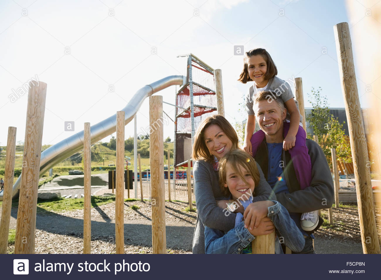 Portrait smiling family at sunny playground - Stock Image