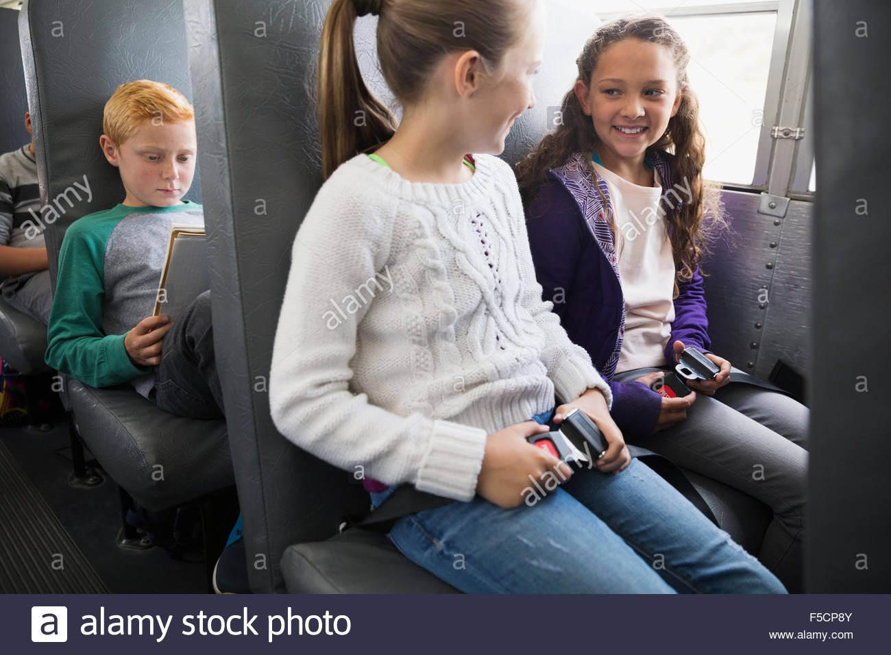 Schoolgirls fastening seat belts on school bus - Stock Image
