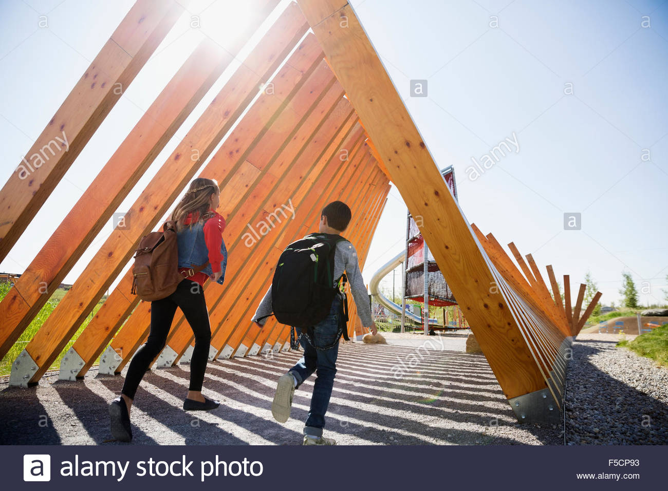 School kids with backpacks running under wood beams - Stock Image