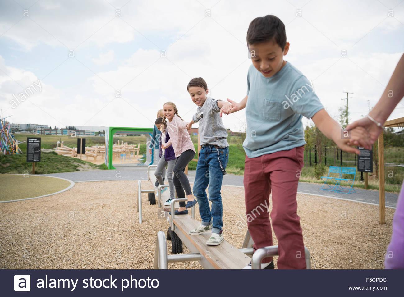 Kids balancing on long seesaw at playground - Stock Image