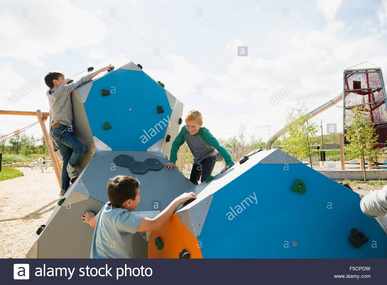 Boys climbing geometric shapes at sunny playground - Stock Image