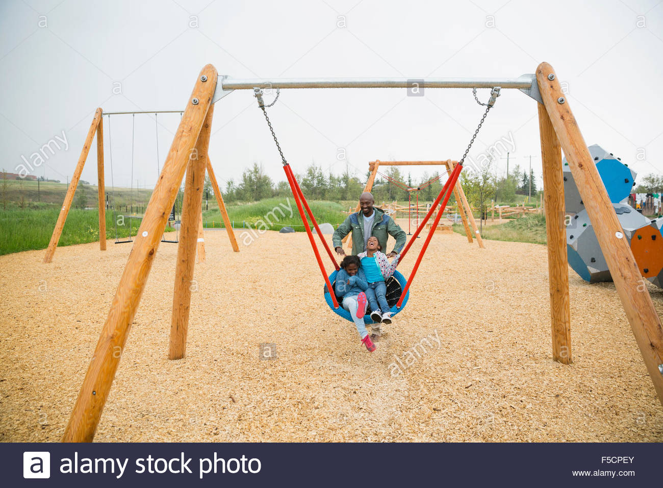 Father pushing daughters in swing net at playground - Stock Image