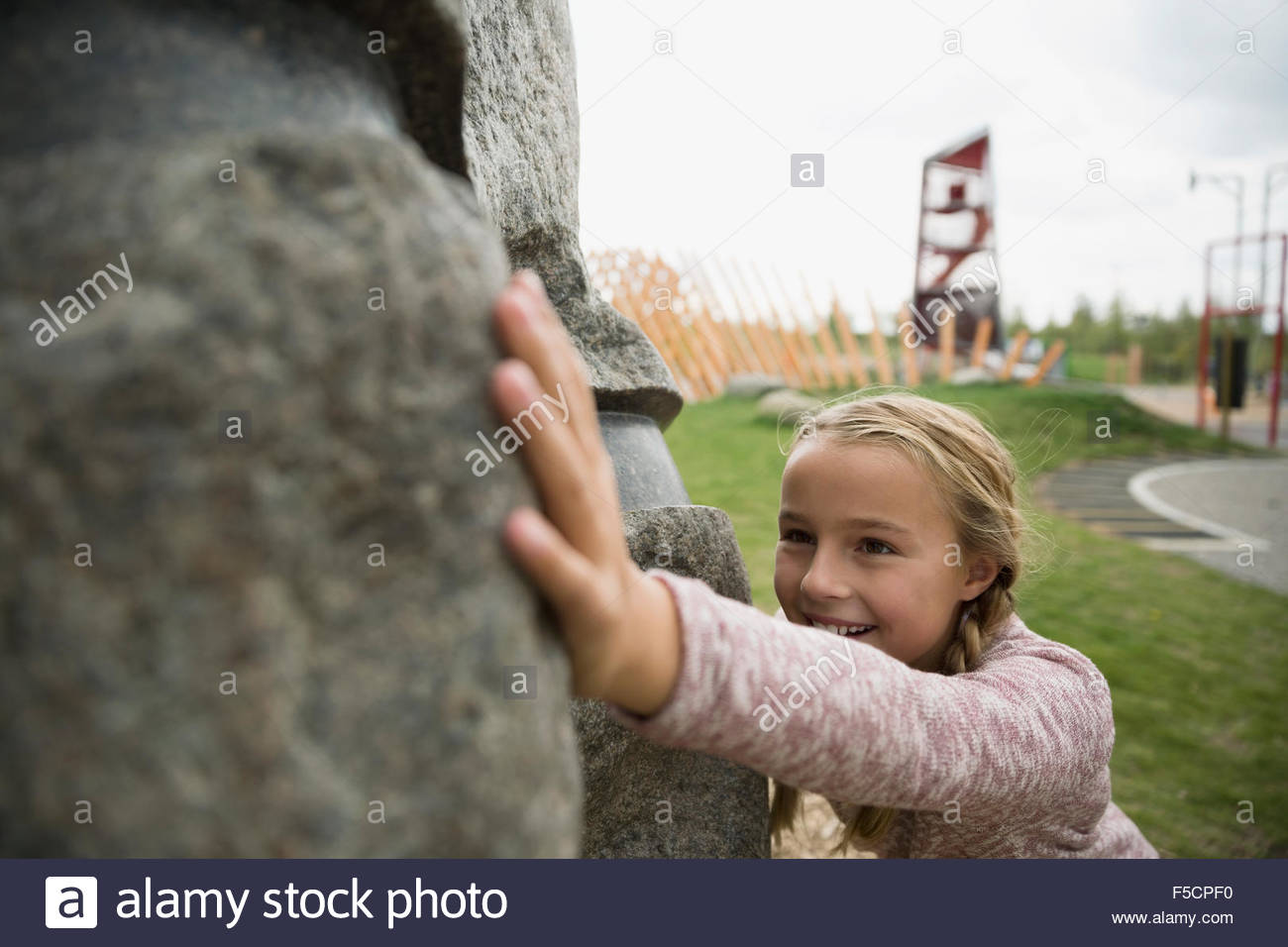 Girl pushing large boulder at playground - Stock Image