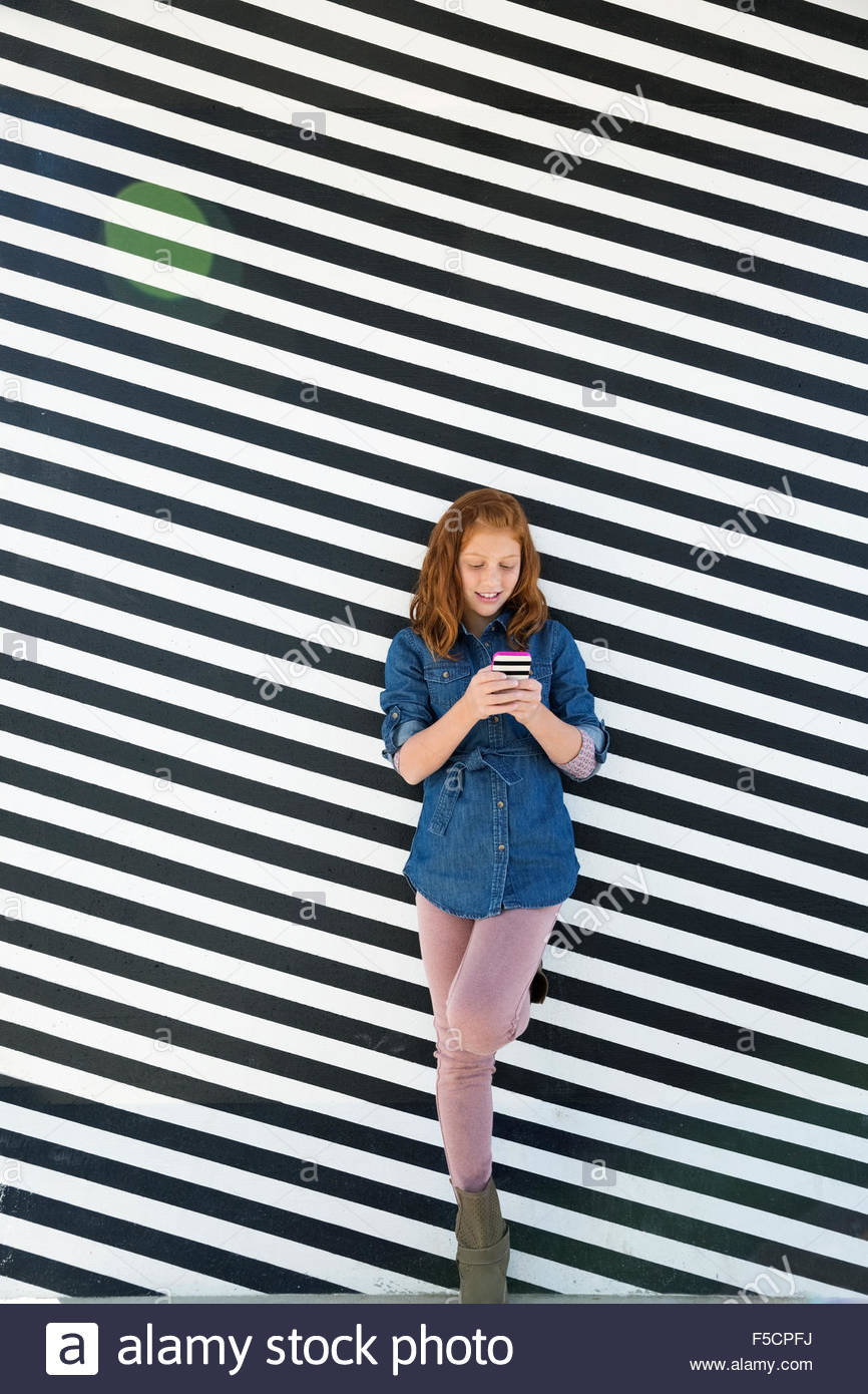 Girl texting against black and white striped wall - Stock Image