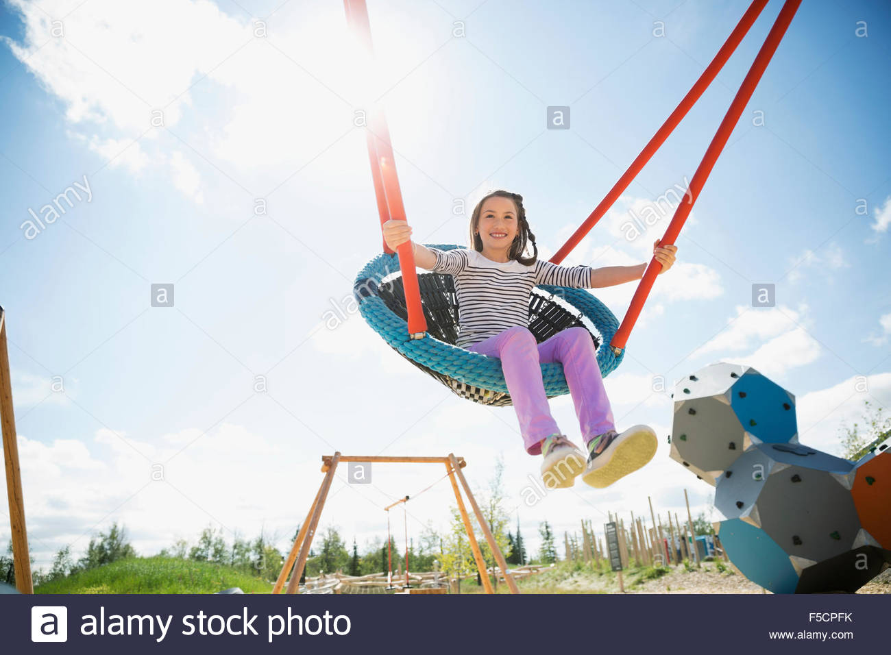 Carefree girl swinging at sunny playground - Stock Image