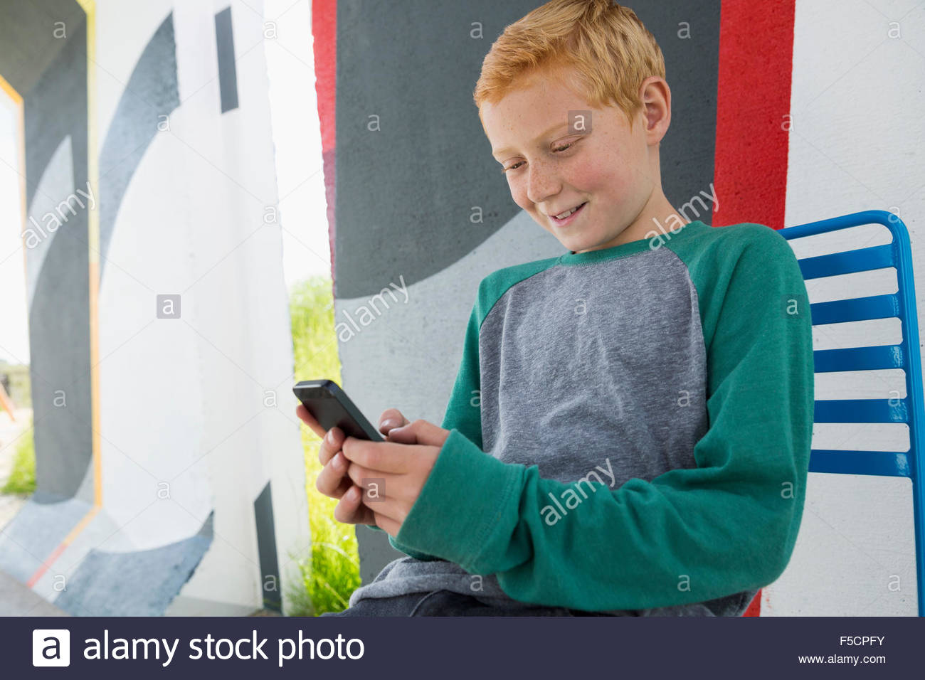 Boy with red hair texting with cell phone - Stock Image