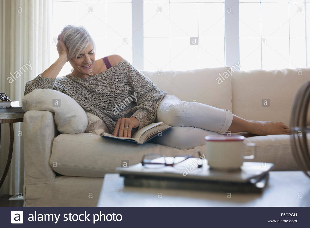 6cb974d2d4f8 Woman reading book and relaxing on sofa Stock Photo  89406257 - Alamy