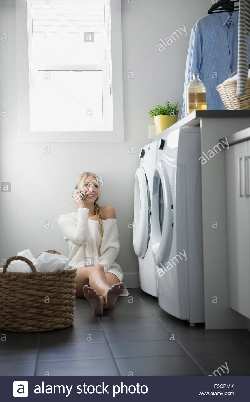 Woman talking on cell phone laundry room floor - Stock Image