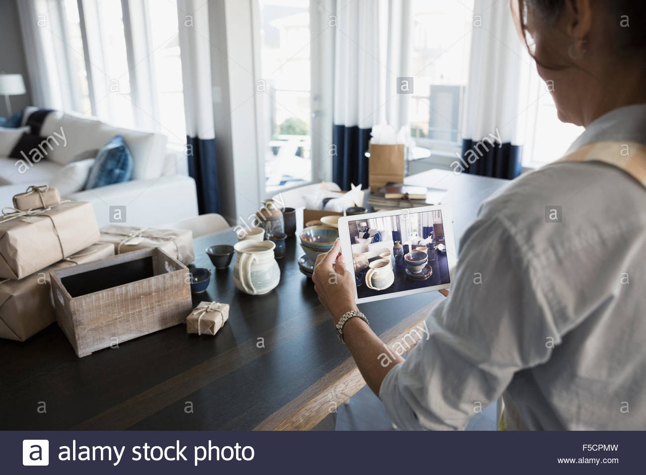 Woman photographing pottery with digital tablet - Stock Image