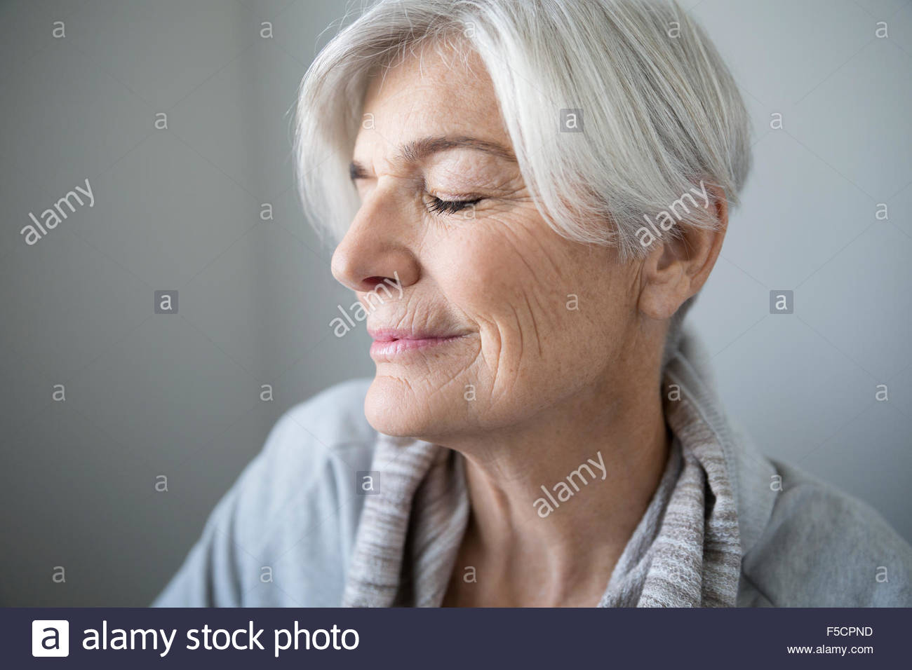 Portrait serene senior woman with eyes closed - Stock Image