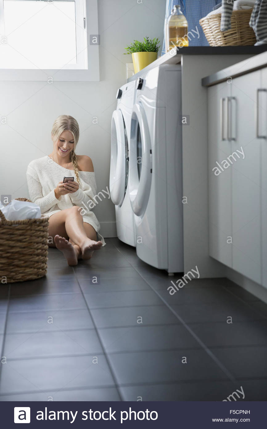 Woman texting with cell phone laundry room floor - Stock Image