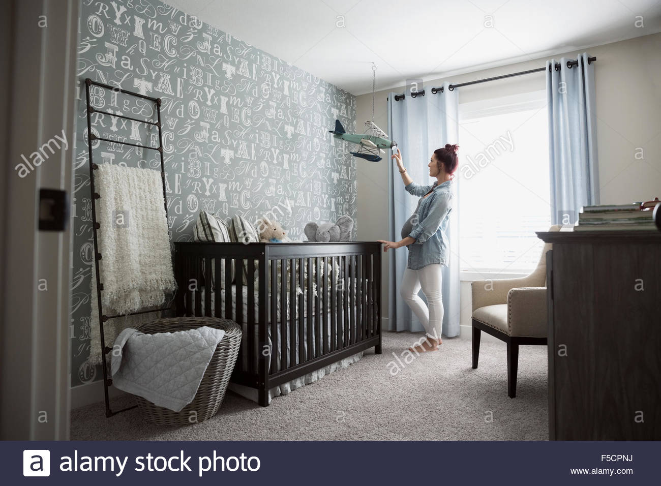 Pregnant woman touching hanging airplane in nursery - Stock Image