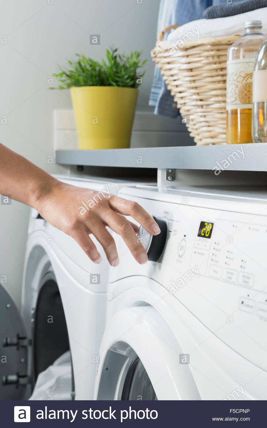 Woman turning washing machine dial in laundry room - Stock Image