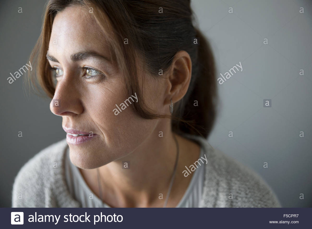 Close up pensive brunette woman looking away - Stock Image