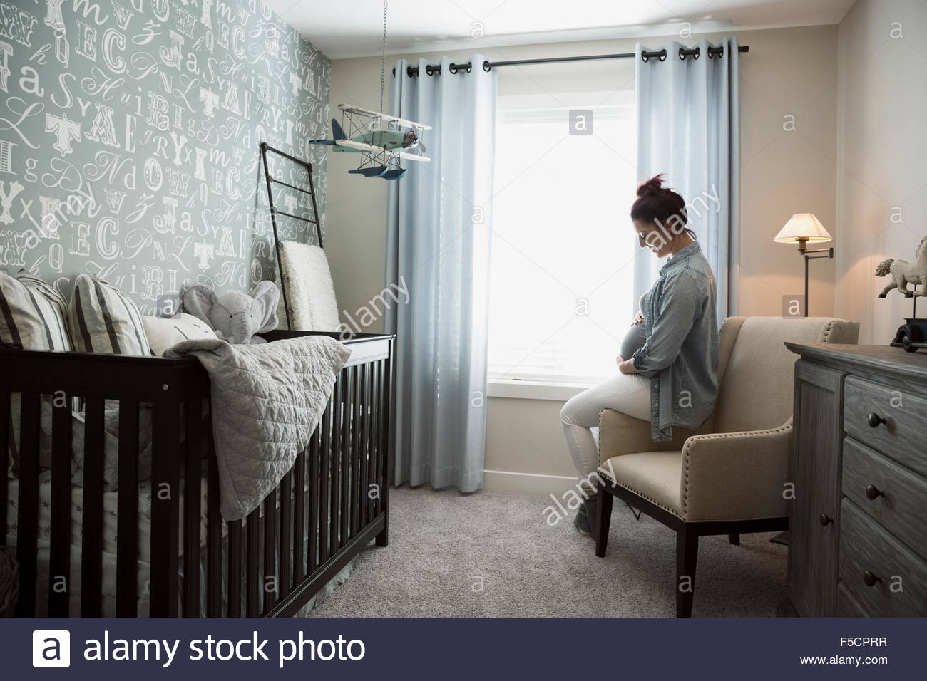 Pregnant woman holding stomach in nursery - Stock Image