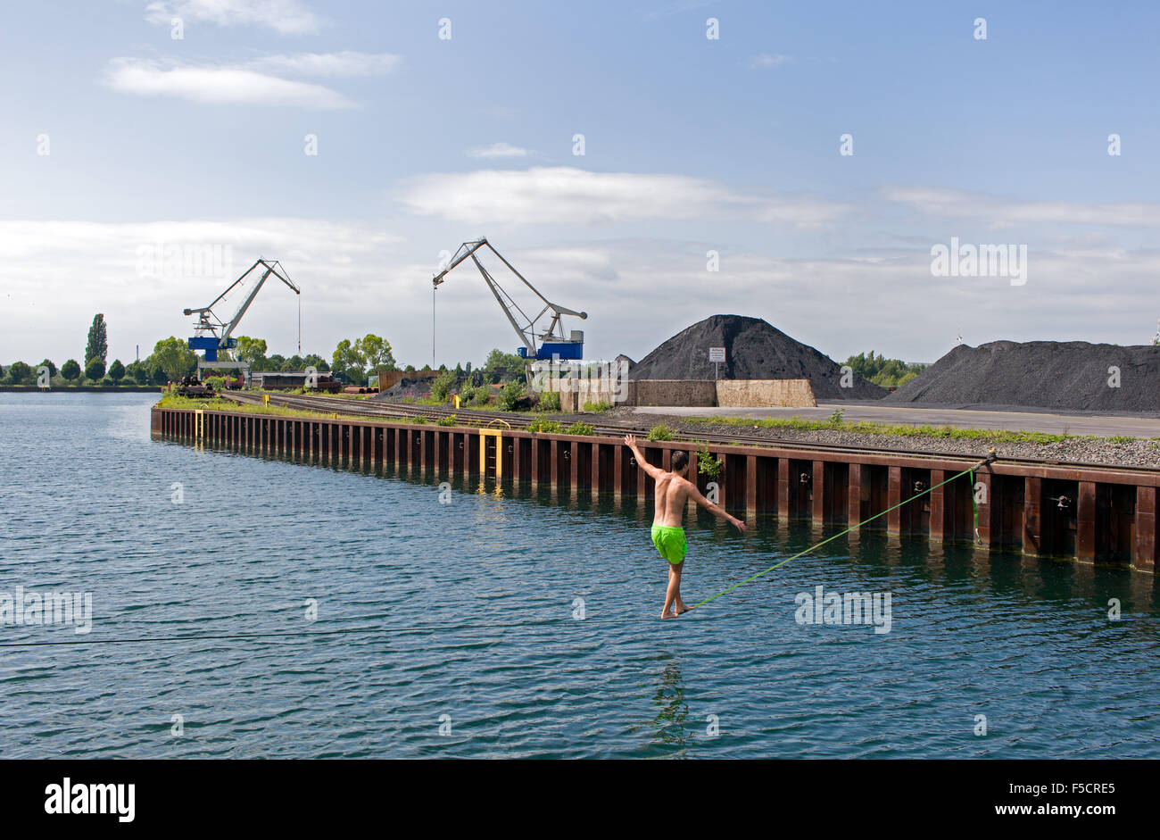 Young guy is slacklining crossing a harbour basin at the inland port of Dortmund - Stock Image
