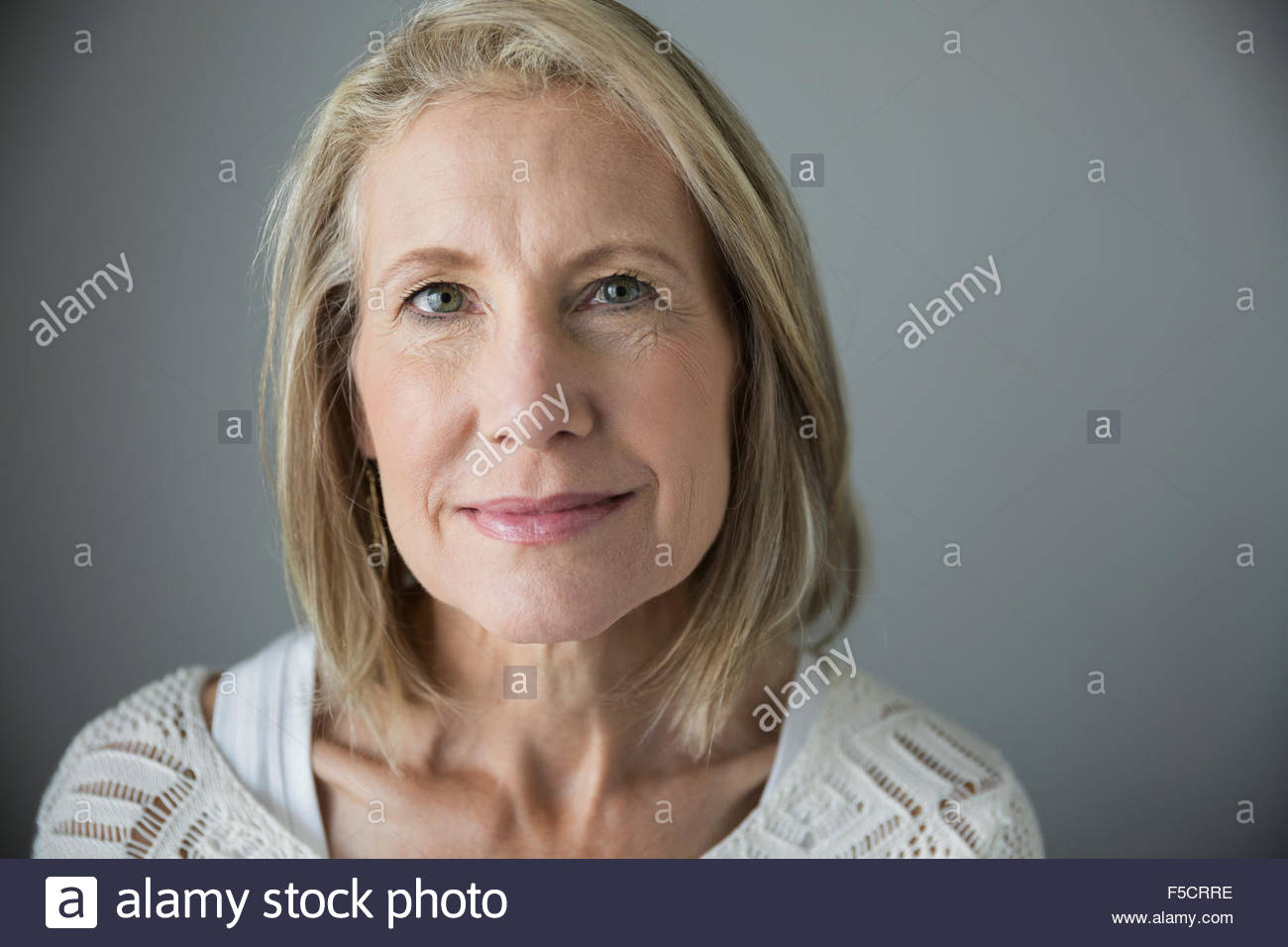 Portrait smiling senior woman with blonde hair - Stock Image