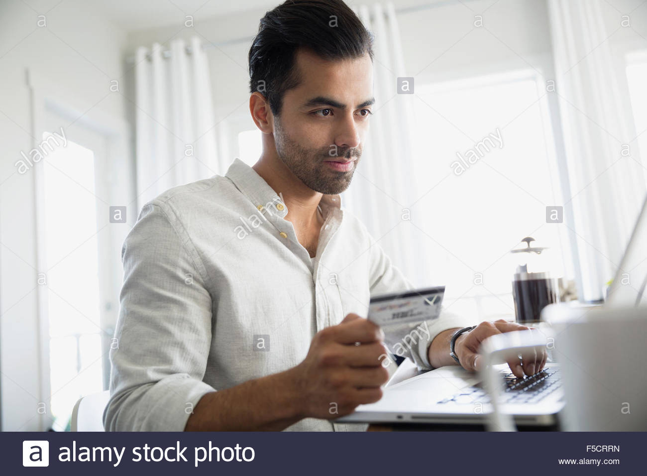 Man with credit card using laptop - Stock Image