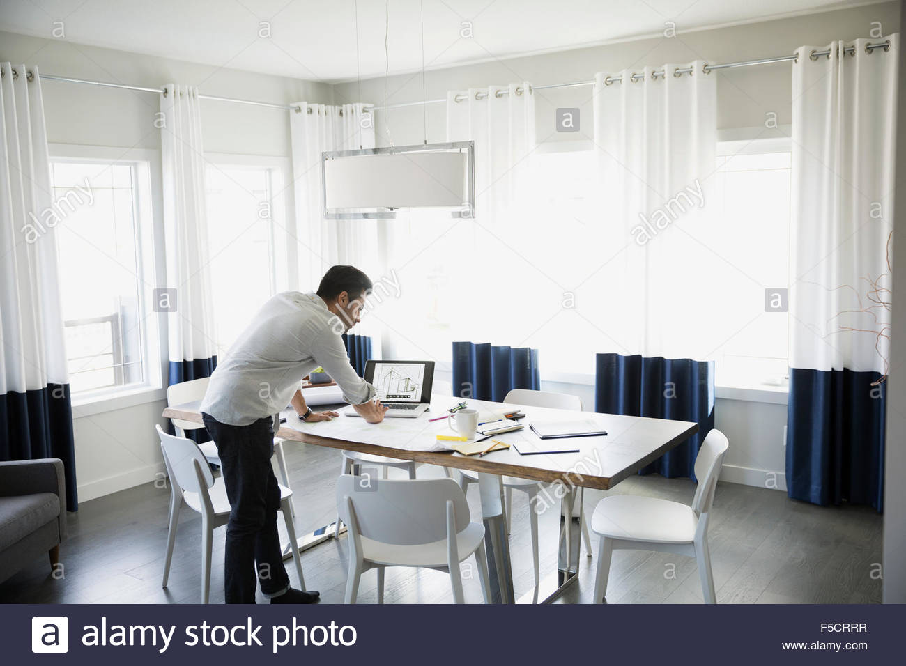 Architect working at laptop on dining table - Stock Image