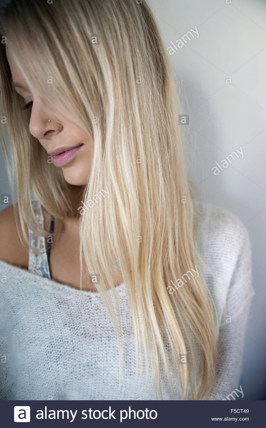 Portrait blonde woman looking down - Stock Image