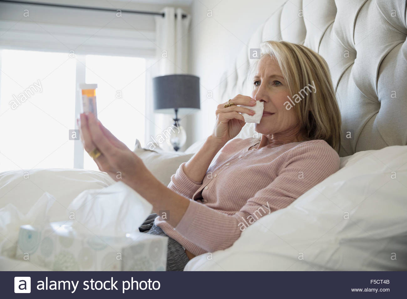 Sick woman with tissues prescription bottle in bed - Stock Image