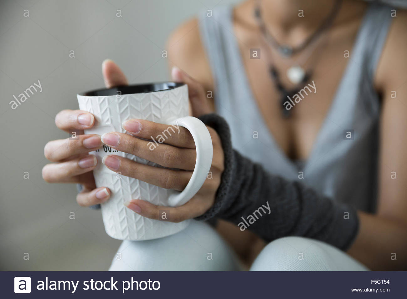 Close up young woman drinking coffee wrist warmers - Stock Image