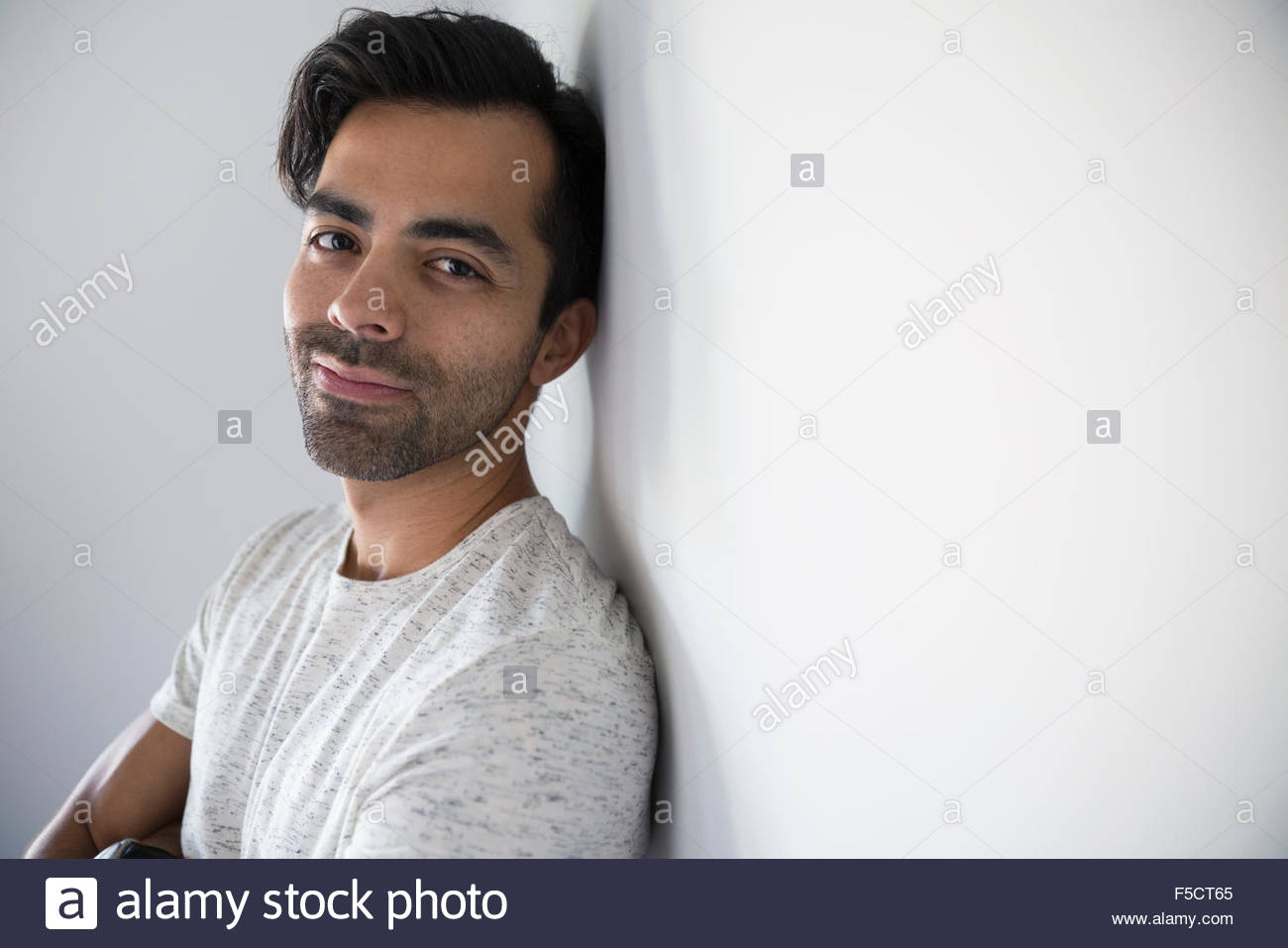 Portrait smiling man with black hair and stubble - Stock Image