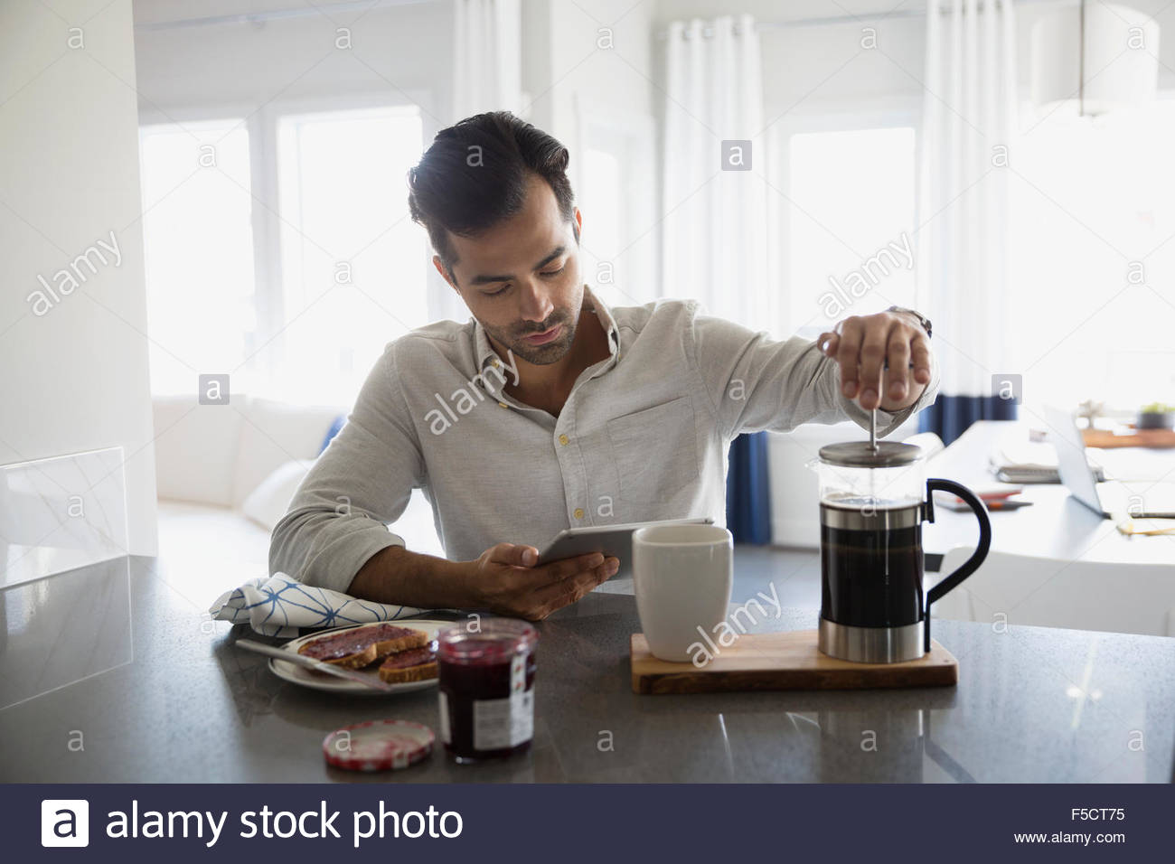 Man with digital tablet making French press coffee - Stock Image