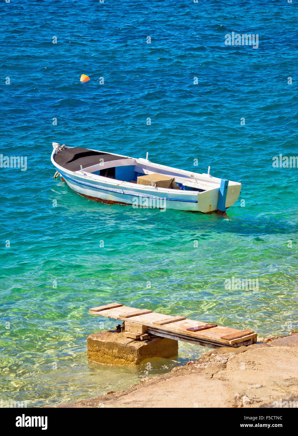 Old wooden fishermen boat on turquoise beach, Mediterranean sea - Stock Image