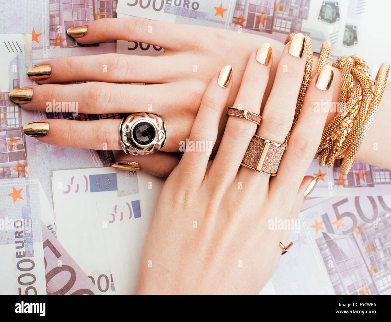 hands of rich woman with golden manicure and many jewelry rings on ...