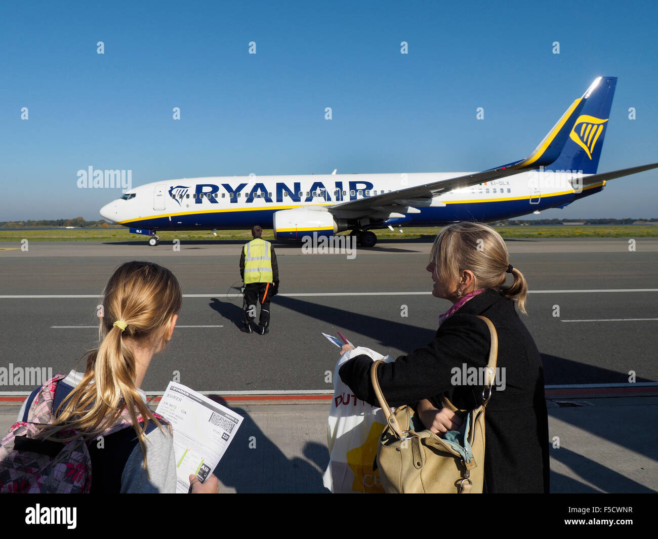 Mother and daughter waiting to board their Ryanair Boeing 737 at Weeze NRN airport - Stock Image