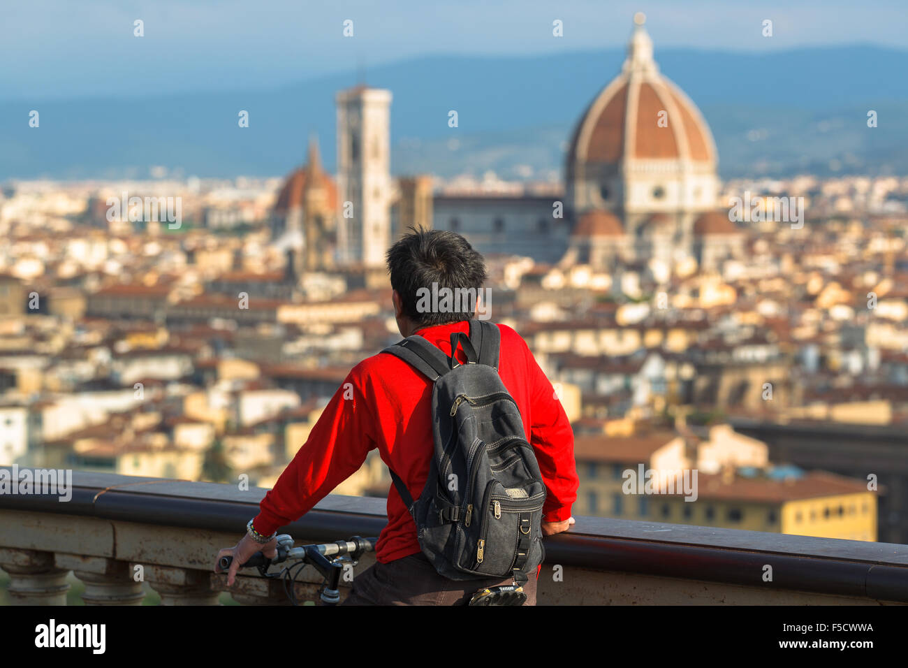 A young man enjoying the view of Santa María del Fiore Cathedral from Piazzale Michelangelo, Florence, Tuscany, - Stock Image