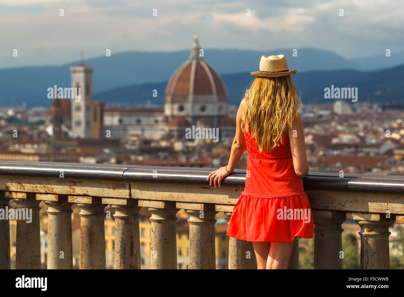 A young woman enjoying the view of Santa María del Fiore Cathedral from Piazzale Michelangelo, Florence, Tuscany, Stock Photo