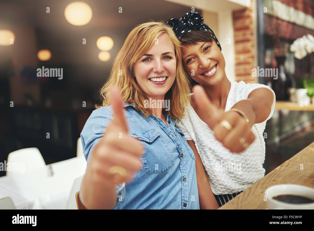 Two happy young female friends giving a thumbs up gesture of approval and success as they sit arm in arm in a cafeteria - Stock Image