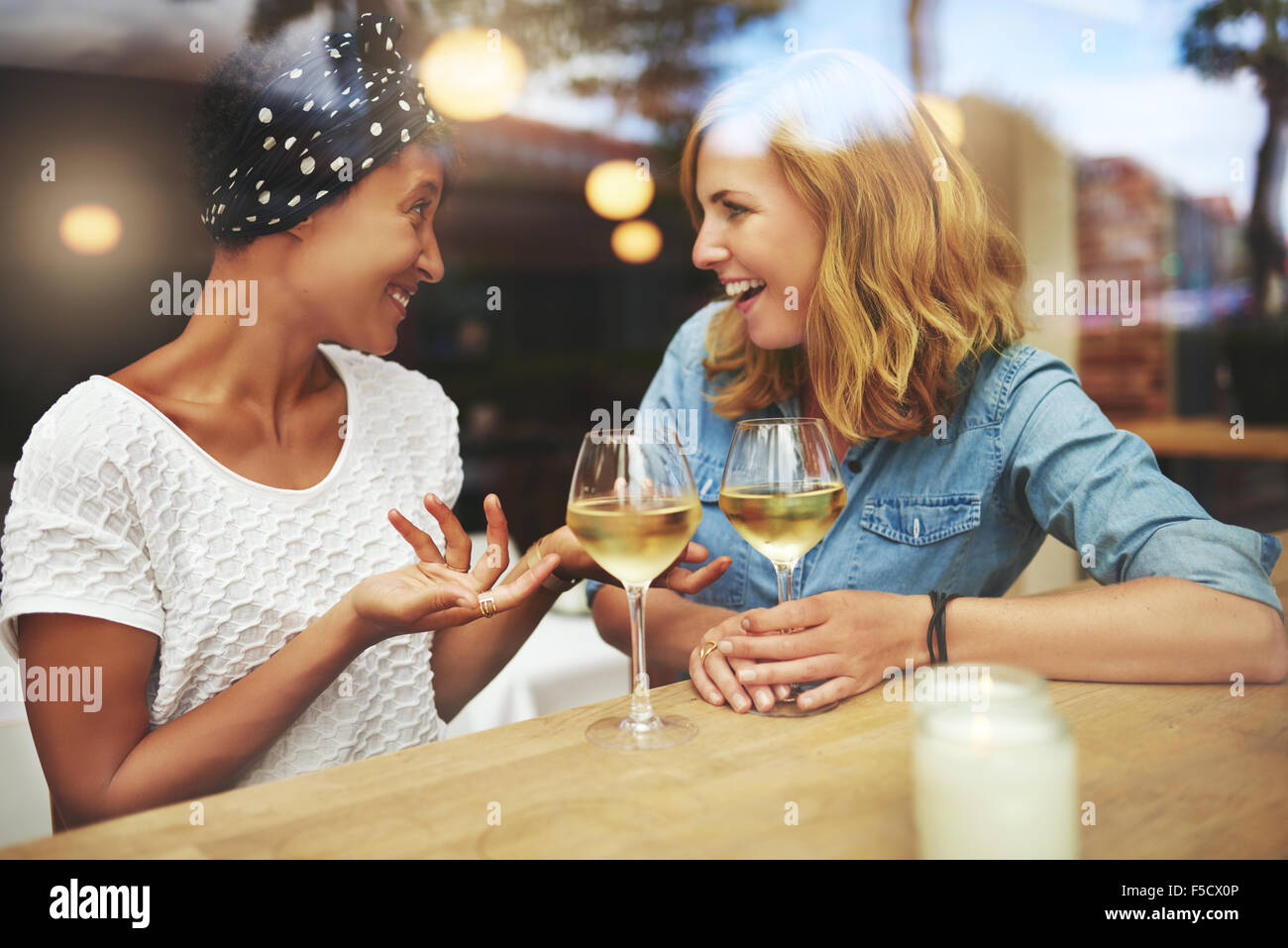 Two attractive women enjoying a glass of white wine together in a pub sitting at a table laughing and chatting with - Stock Image