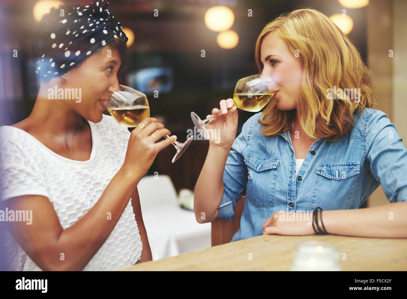 Two attractive young women meeting up in a pub for a glass of white wine sitting at a counter smiling at each other - Stock Image