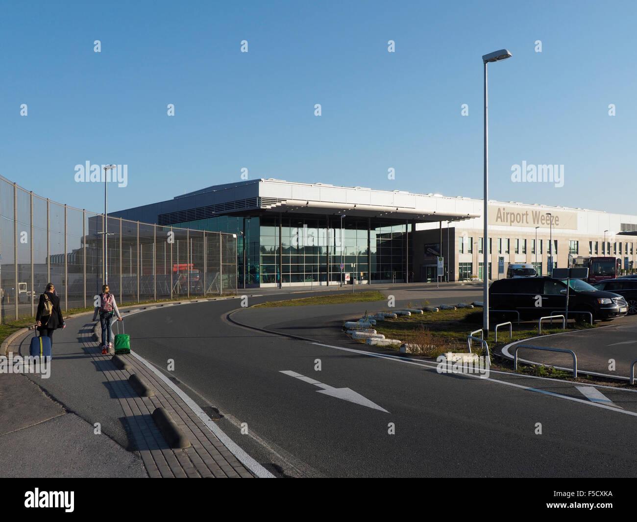 Weeze Niederrhein airport terminal exterior with travelers people Ryanair NRN - Stock Image