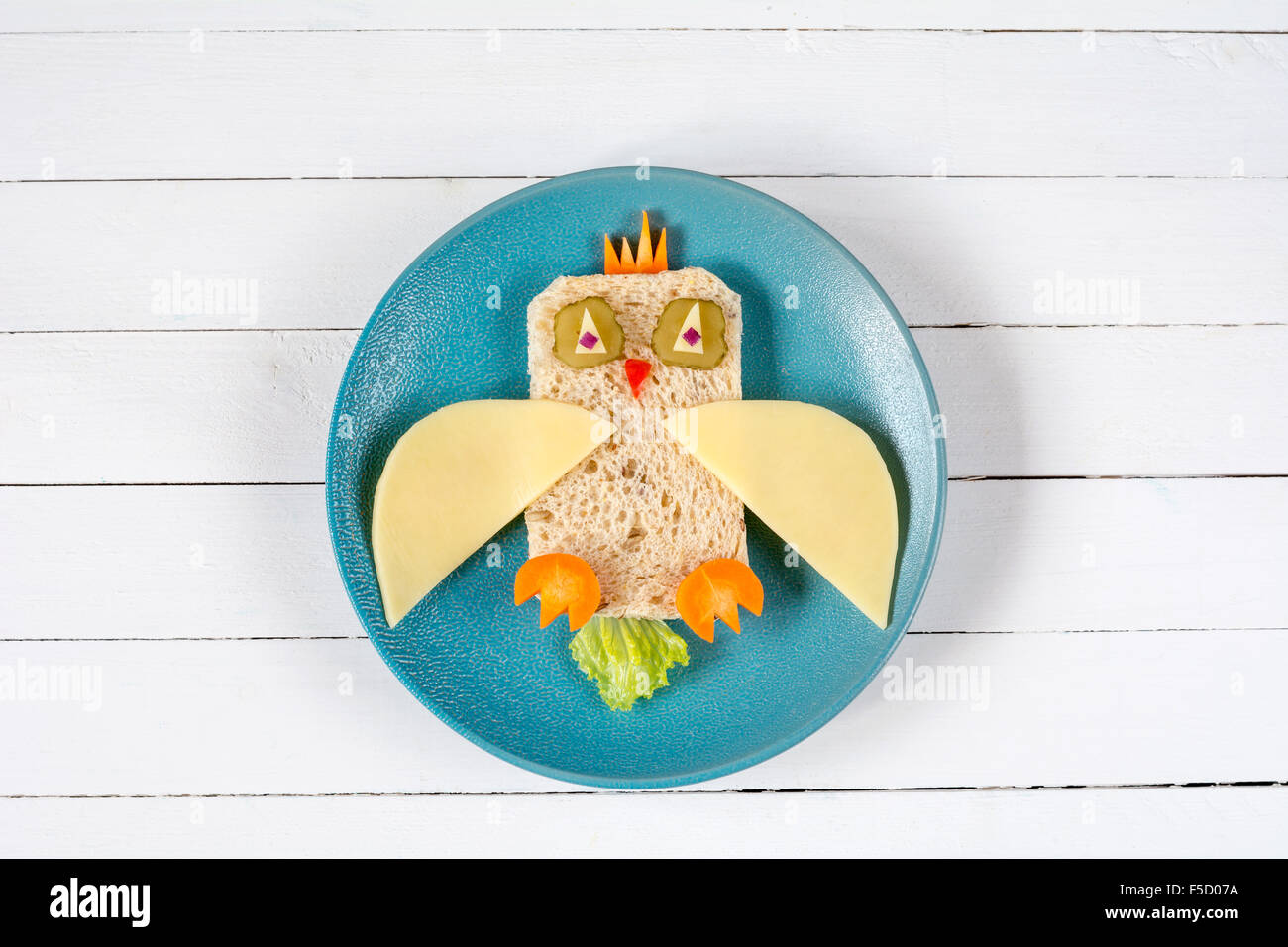 Funny sandwich owl for kids on plate, healthy breakfast or school lunch. Isolated on white wooden table Stock Photo