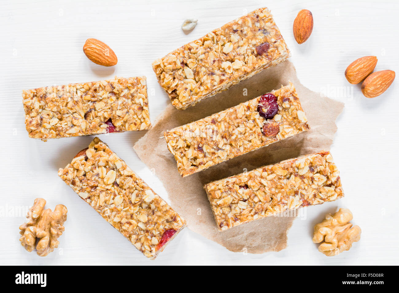Granola Bar Or Energy Bar With Oats, Dates And Nuts On White Wooden  Background, Top View