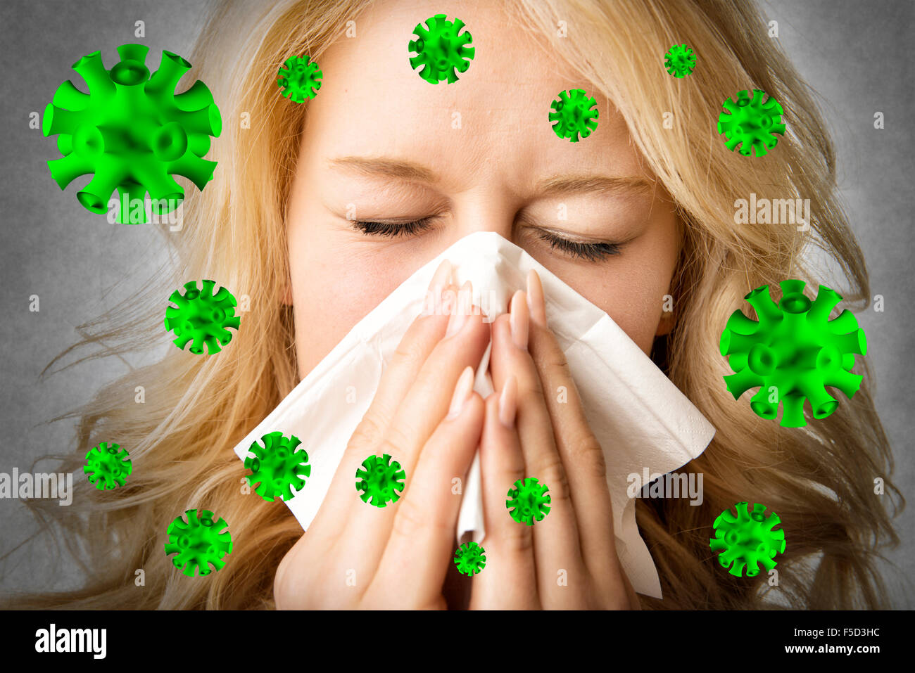 Portrait of a ill blond woman who is sneezing virus  in a tissue - Stock Image