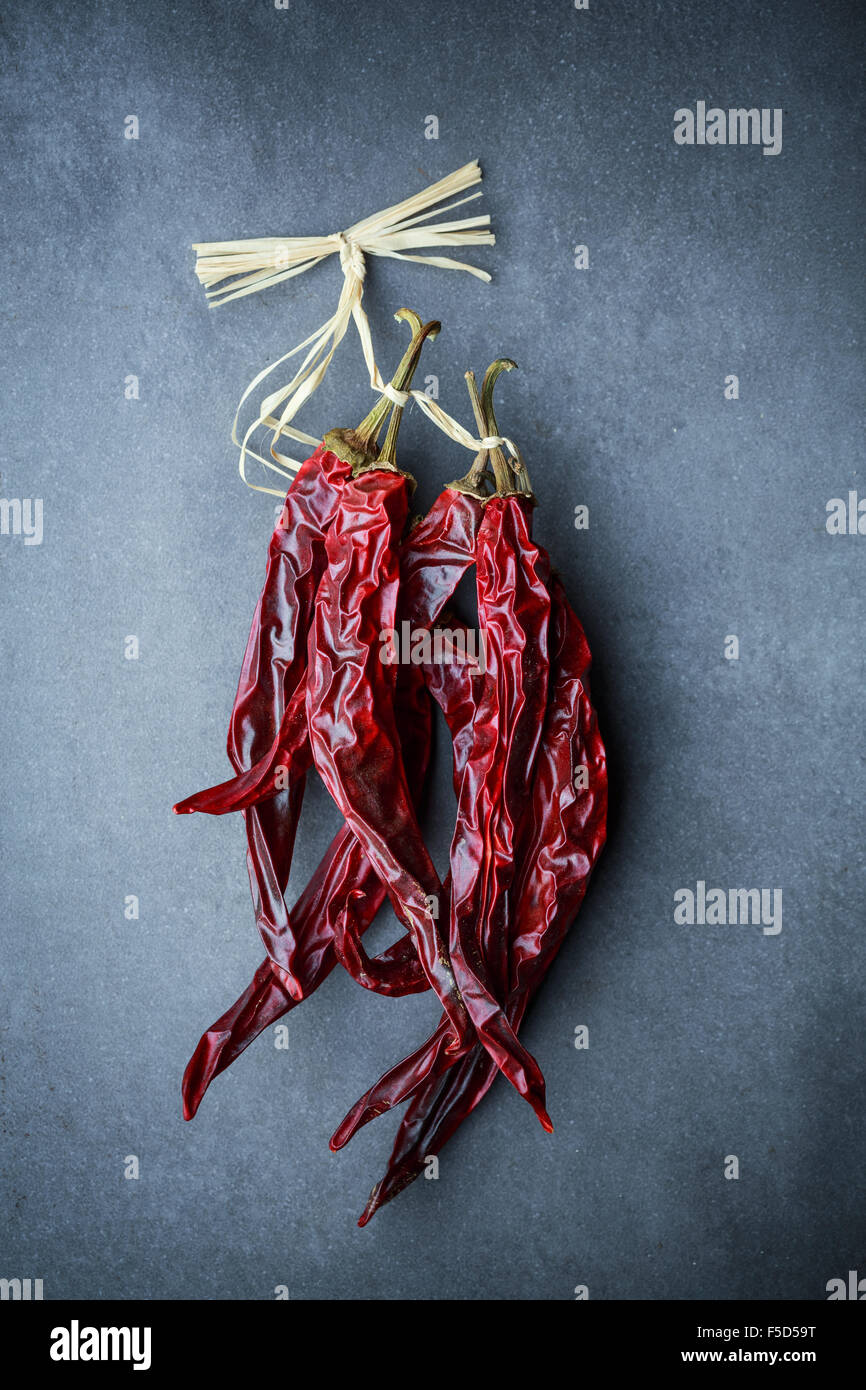 Dried hot red chili peppers on dark background - Stock Image